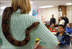A Trinity High School biology teacher introduces Lucy, a red-tailed boa, to visiting sixth-grade students in Euless, Texas. Middle and high school teachers consistently rated factual knowledge of science more important, while college professors most wanted students to be able to understand a hypothesis.