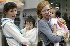 American women stroll with their newly adopted Chinese babies in Guangzhou, the capital of Guangdong province in southern China, in this April 2003 file photo. Russia has joined China and Guatemala in curtailing adoptions by Americans.