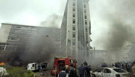 Rescue services and investigators inspect the scene of a suicide car bomb which exploded near the prime minister's headquarters in central Algiers Wednesday.