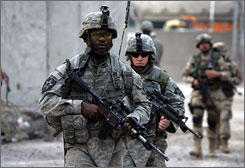 U.S. Army soldiers conduct a joint patrol with Iraqi Army soldiers in southern Baghdad last month. Bonuses paid out by the military have soared to entice troops to stay in uniform.