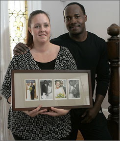 Michelle and James Cadeau pose at their home in West Orange, N.J., with photos from their wedding in 2001. Michelle is from Sweden, and James, from Haiti.