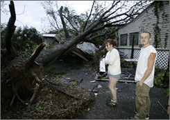 Amanda Rymer, left, and her husband Nelson Decker survey the damage to their carport and garage area, rear, after a tree was knocked down onto it by a severe storm that swept through the area in Haltom City, Texas, Friday.