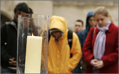 Boston University students pray at a candle lit for victims of the Virginia Tech massacre. The shootings have some universities looking at their policies on background checks on applicants.