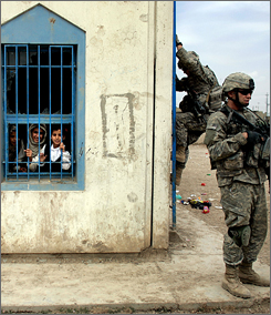 School children watch as U.S. soldiers climb to the roof of their school to get a high vantage point April 15 in Baghdad. The soldiers are part of the United States military surge as they try to help control the violence plagued city. 