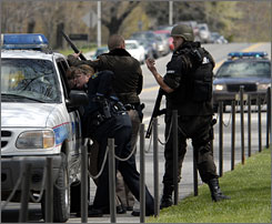 State and local police wait for a building to be cleared at the Virginia Tech campus following the deadly shooting.