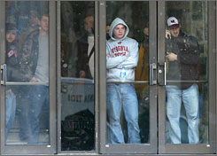 Virginia Tech students watch from the doorway of McBryde Hall on the Virginia Tech campus as police infiltrate the area where a shooting took place.