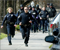 Blacksburg police officers run from Norris Hall on the Virginia Tech campus Monday. The public university remained in lockdown mode Monday night after a shooting spree left dozens dead in the academic hall.