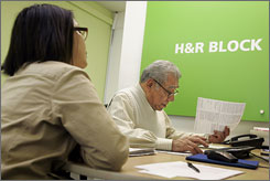 H&R Block senior tax advisor Bacho Medina, right, helps JoAn Ramos with her taxes at an H&R Block office in San Francisco, Monday.