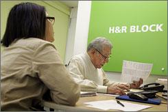 H&R Block senior tax advisor Bacho Medina, right, helps JoAn Ramos with her taxes at an H&R Block office in San Francisco, Monday.