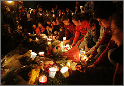 Virginia Tech students create a shrine of flowers and candles Tuesday night in memory of the victims of Monday's campus shootings.