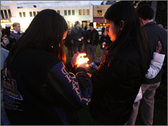 Virginia Tech students Rachel Rizk, 22, left, and Raksha Vasudevan, 22, light a candle at a vigil for victims of a shooting on the university's campus.