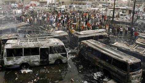 Iraqis gather at the site of a car bomb explosion in Baghdad's al-Sadriyah neighborhood, Wednesday, in which over a hundred people were killed. The wave of car bombings wounded hundreds in five different locations, as insurgents ripped through a massive Iraqi and U.S. security crackdown in the capital.