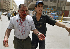 A wounded Iraqi evacuates the site of a roadside bomb in Baghdad's al-Jumhuriyah street on Wednesday.
