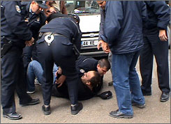 Turkish police officers wrestle an unidentified man down following an attack at a publishing house in the city of Malatya. Attackers slit the throats of three people at a Turkish Bible publisher's on Wednesday, the latest attack on minorities in the mainly Muslim country.