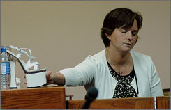 Mary Winkler places a platform heel on the witness stand during her murder trial. Her husband allegedly wanted her to wear the shoes and a wig during sex.