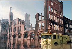 Firefighters cruise past the shell of a burned-out building in downtown Grand Forks, N.D., on April 20, 1997.