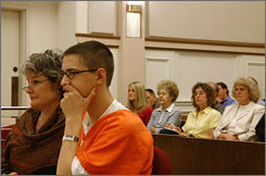 Eric Hainstock, right, sits next to his public defender, Rhoda Ricciardi, during a hearing in Baraboo, Wis. At right is the family of John Klang.