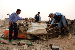 Iraqi police inspect a blast scene where a suspected al-Qaida suicide bomber smashed a truck loaded with TNT and toxic chlorine gas into a police checkpoint in Ramadi, Iraq, April 6.
