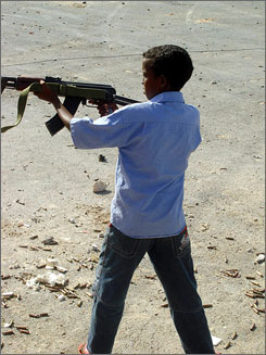 A 10-year-old Somali boy aims his AK-47 rifle at an Ethiopian military base near the capital. Artillery shells and mortars continue to rain down on Mogadishu for a seventh straight day Tuesday, despite the U.N.'s plea to end violence that has left hundreds dead.