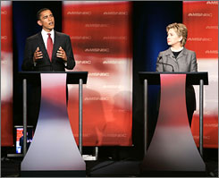 Democratic candidate Sen. Barack Obama, left, answers a question as Sen. Hillary Clinton looks on during the first debate of the 2008 presidential campaign Thursday night.