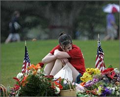 Celeste Leizer, 19, mourns while sitting next to her friend Caitlin Hammaren's memorial stone on the Virginia Tech campus in Blacksburg, Va.