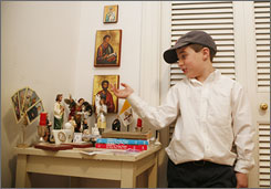 "James Higgins, 7, with a table full of statues of Catholic icons. His parents consider him their miracle child. He was born 10 weeks premature. Around age 3, he became infatuated with Mary. Since then, his mother said simply, being Catholic ""is a way of life for him."""