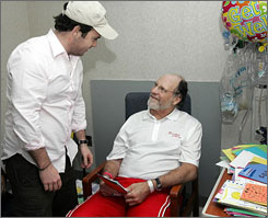 New Jersey Gov. Jon S. Corzine smiles as he greets son Jeff Corzine, while looking through get well cards in his hospital room.
