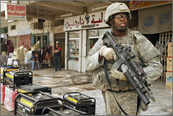 A U.S. soldier patrols Baghdad on Sunday. Five fellow soldiers were killed in the city this weekend, making April the deadliest month for the U.S. this year.