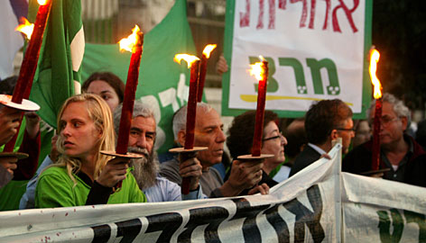 "People hold candles and a sign reading ""Take Responsibility"" during a protest calling for Olmert's resignation outside the official residence in Jerusalem on Monday."