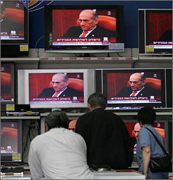Israeli's watch the news on large television's showing Olmert on Monday.