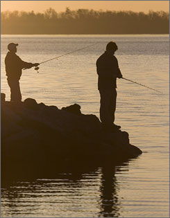 Two men enjoy the early morning sunrise as they fish along the shore of Lake Ontario in Kingston, Ontario, on April 20. An Ebola-like virus has been killing fish in several Great Lakes, including Lake Ontario.