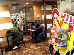 Several men rest on their arms at a downtown McDonald's in Hong Kong early Tuesday, May 1.