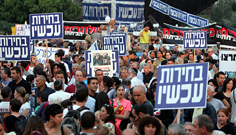 "Israelis holding banners that read ""Elections Now"" gather in Tel Aviv's Rabin Square."