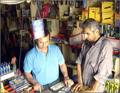 Mahmoud al-Dabbagh, left, assists shopper Jabbar Ali at the Tuhama hardware store on Baghdad's Rasheed Camp Road.