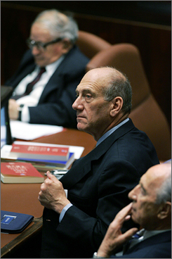 Olmert flanked by Vice Prime Minister Shimon Peres, right, and Minister For Pensioner Affairs Rafi Eitan in the Israeli parliament on Thursday.