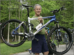 President George W. Bush lifts his bicycle before taking a mountain bike ride in Beltsville, Md.
