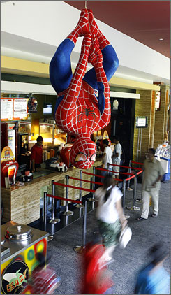Indian movie goers walk under a Spider-Man display hanging from the ceiling at a multiplex in Mumbai, India. Spider-Man 3 not only set a mark for a movie's U.S. opening weekend, it smashed box office records across eight Asian markets where it opened earlier this week.