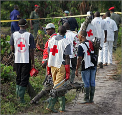 Cameroon troops secure the area as rescue workers walk towards the crash site of a Kenya Airways plane on Monday.