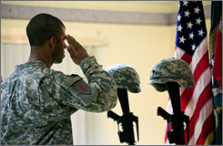 An unidentified U.S. soldier pays his respects to two fallen comrades at a memorial service in Baghdad.