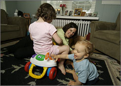 Graphic designer Kathleen Falk, 35, plays with her son, Andrew, who turns 1 on May 17, and her daughter, Lauren, who turns 4 on May 30, in their St. Louis home.