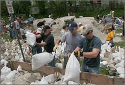 Sandbaggers load a truck trailer along the Katy Trail in Rocheport, Mo., Tuesday.