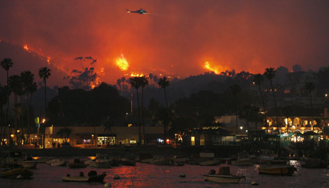 A fire fighting helicopter passes over a raging wildfire as it approaches Santa Catalina Island's main town of Avalon, Calif., Thursday.