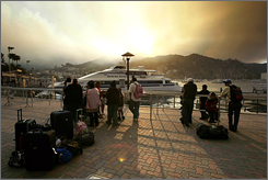 People wait to be evacuated from the town of Avalon, Calif., as smoke from a wildfire rises in the background on Catalina Island Thursday. The 400-acre wildfire erupted on Thursday, forcing evacuations just as firefighters were mopping up a blaze at Los Angeles' sprawling Griffith Park.