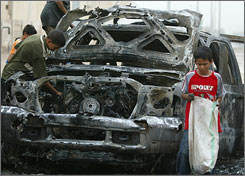 Iraqi children search for parts in the remains of a vehicle which was part of a convoy hit by a roadside bomb, in north Baghdad, Friday.