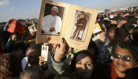 Many hold pictures of Pope Benedict XVI and of Antonio Galvao, known as Friar Galvao, an 18th-century Franciscan monk who is credited by the church with 5,000 miracle cures, during his canonization mass in Sao Paulo, Brazil, Friday.