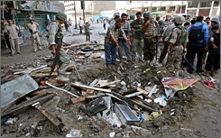 Iraqi soldiers and civilians survey the scene following a car bomb attack in Baghdad. The blast killed at least 17 and injured 46.