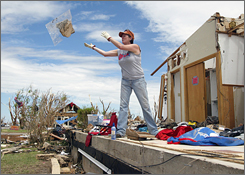 Rhonda Engelken clears debris from her home Thursday in Greensburg, Kan. Engelken plans to rebuild in the same location.