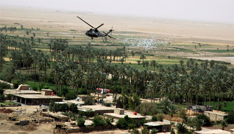 A U.S. helicopter drops reward leaflets over Owesat Village, Iraq, Monday. The leaflets, bearing tip-line phone numbers and information about three US soldiers missing after an ambush Saturday, were dropped over villages in the area to encourage local residents with information about the soldiers to tell coalition forces their whereabouts. See           photos of the search.