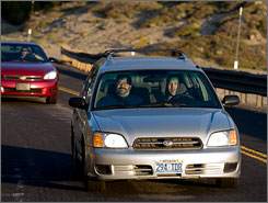 Joe Savage, at the wheel, and John Mueller, drive up Mt. Rose Highway in Reno on Wednesday. Rising gas prices have forced the music teachers to carpool to save money.
