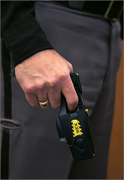 A police officer holds a Taser X26 stun gun, which has been criticized for causing injury. Miami's medical treatments for those shocked by stun guns could improve public confidence, law enforcement officials say.